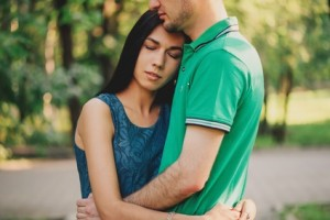 Young beautiful woman and young man embracing each other in summer park, tender scene. Couple in love